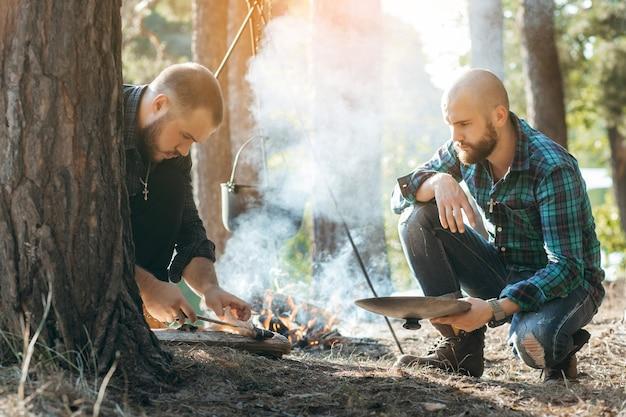 森で魚をナイフで切る2人の男性