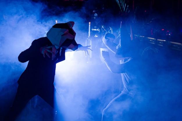 クラブのパーティーでポーズをとっている動物のマスクを持つ2人の男性