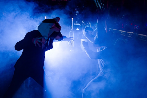 Two men with animal masks posing at the party in the club