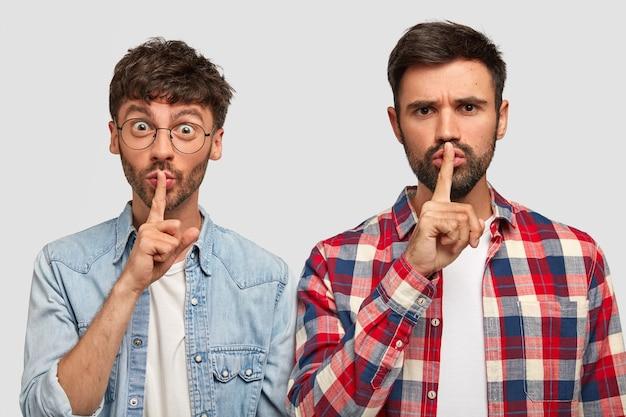 魅力的なルックスの2人の男性が沈黙のジェスチャーをし、人差し指で唇に触れます