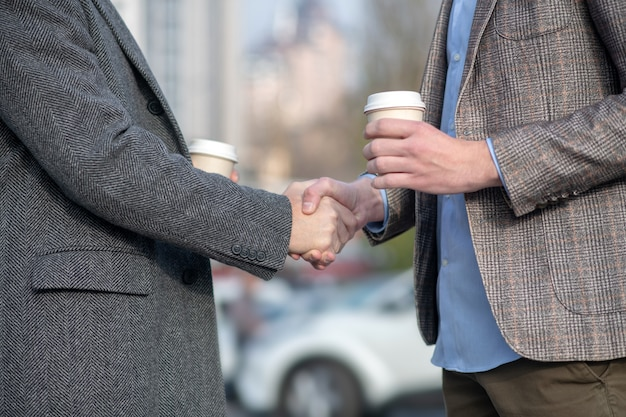 Two men with coffee cups shaking each others hand while meeting in the street
