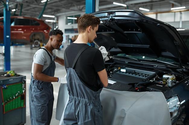 Двое рабочих ремонтируют двигатель в механической мастерской.