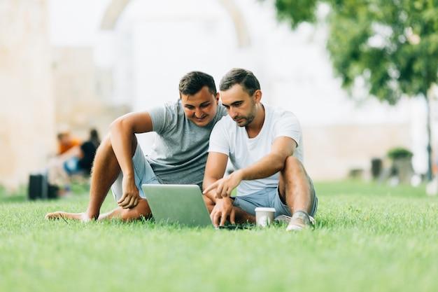 Due uomini che lavorano con il laptop sul verde al park