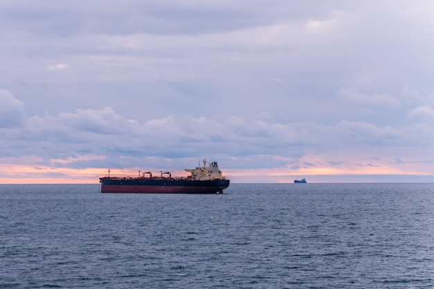 Two merchant ships in calm waters at sea.