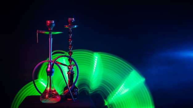 Two metal hookahs with glass flasks with shisha charcoals in smoke with green neon glow on a dark background