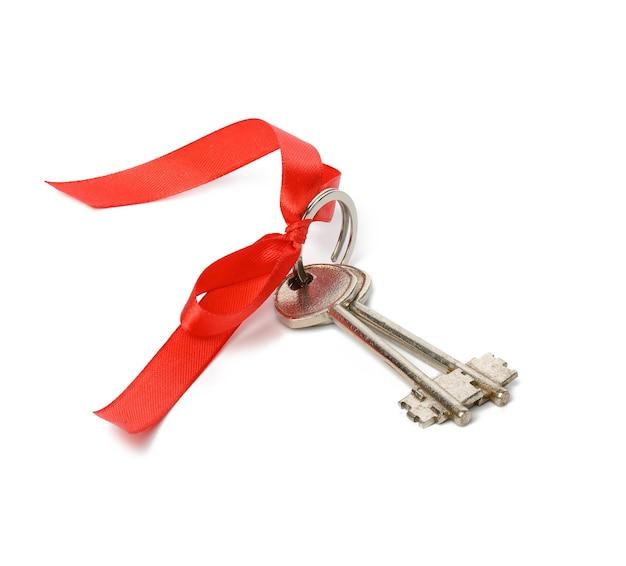 白い背景で隔離の赤いリボン、不動産購入コンセプトの2つの金属製の家のドアの鍵