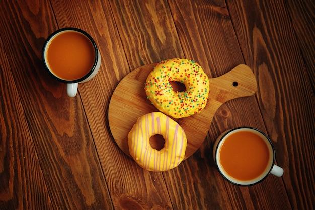 Две металлические кружки с тыквенным соком с пончиками