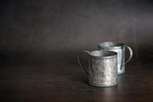 暗い灰色の背景に2つの金属の古いカップ