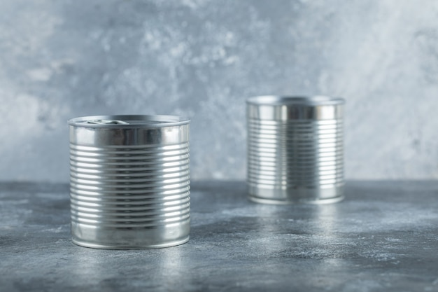 Two metallic cans on marble.
