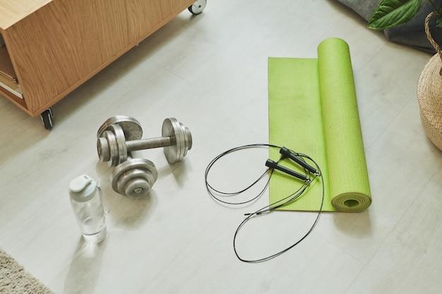 Две металлические гантели, скакалка, пластиковая бутылка с водой и свернутый зеленый коврик для занятий на полу в домашней комнате.