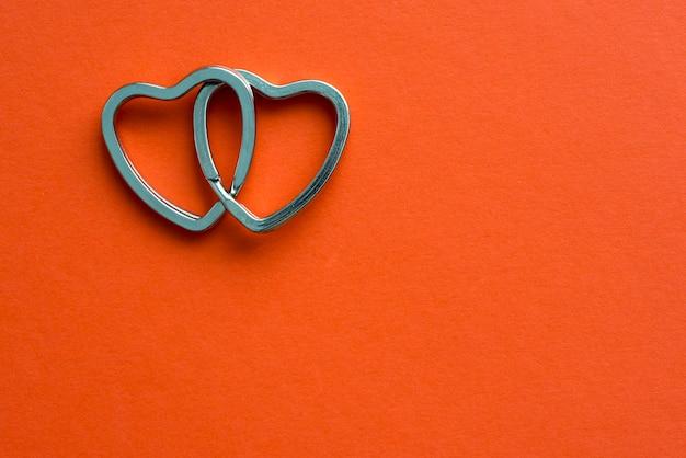 赤い背景にリンクされている2つの金属の心