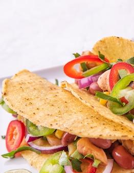白い背景の上のサービングプレートに鶏肉、玉ねぎ、唐辛子、トウモロコシ、豆と2つのメキシコのタコス。マクロとクローズアップビュー