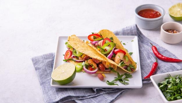ライムとスパイスを添えたサービングプレートにチキン、タマネギ、チリペッパー、コーン、豆を添えた2つのメキシコのタコス。フラットレイとコピースペース