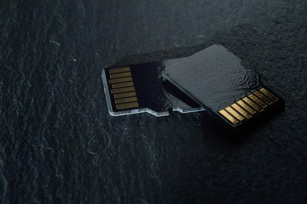 두 개의 마이크로 sd 카드는 어두운 질감의 배경에 서로 겹쳐져 있으며 상단에는 금색 접점이 있습니다. 확대.