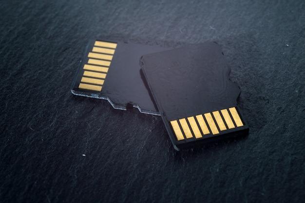 두 개의 Micro Sd 카드가 어두운 질감 배경 위에 서로 위에 놓여 있으며 상단에 황금색 접점이 있습니다. 확대. 프리미엄 사진