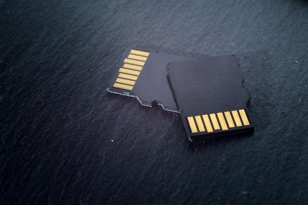 두 개의 micro sd 카드가 어두운 질감 배경 위에 서로 위에 놓여 있으며 상단에 황금색 접점이 있습니다. 확대.