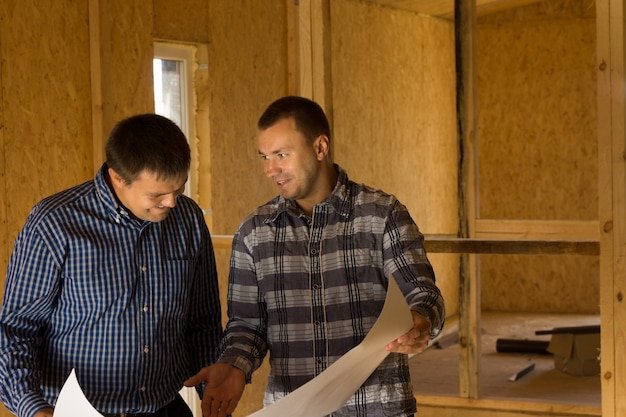 Two middle age architect men discussing the building interior design at the construction site.