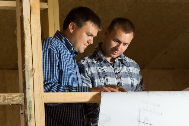 Two middle age building architects reviewing building blueprint at the site seriously.