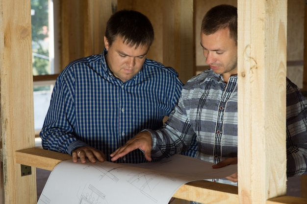 Two middle age building interior designers talk about the proposed design on blueprint.