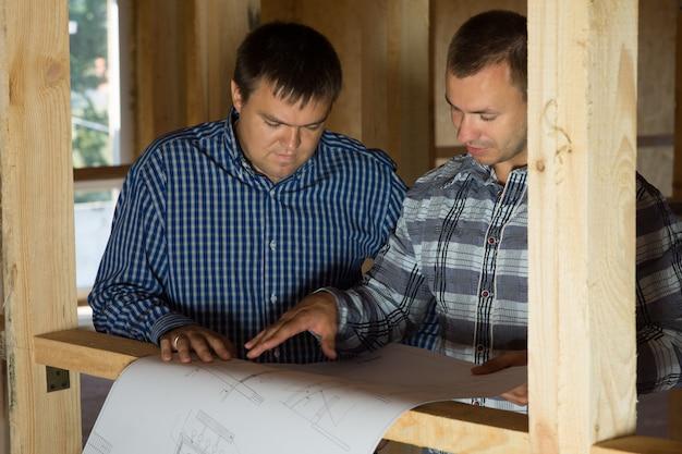 2人の中年の建物のインテリアデザイナーが青写真で提案されたデザインについて話します。