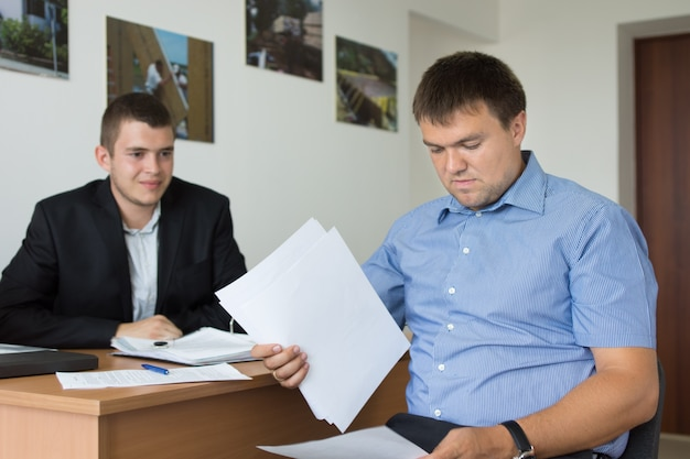 Two middle age male engineers reviewing project documents at the office