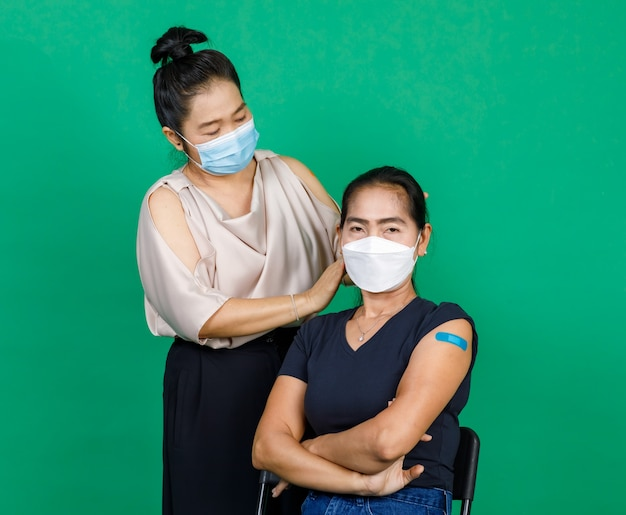 Two middle aged asian women wearing masks showing their arms with bandage patch showing they got vaccinated for covid 19 virus on green background. concept for covid 19 vaccination.