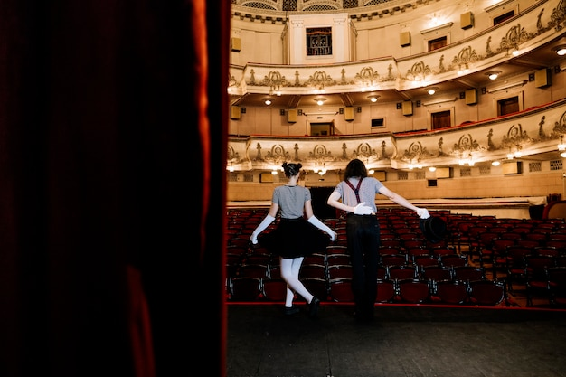 Two mime artist bowing in an empty auditorium