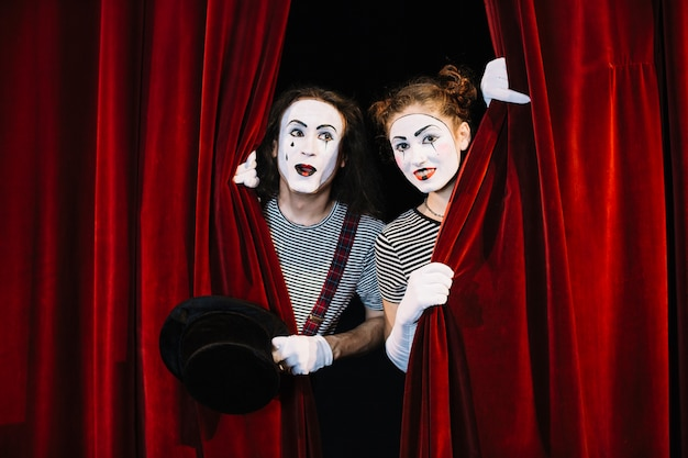 Two mime artist peeking through red curtain