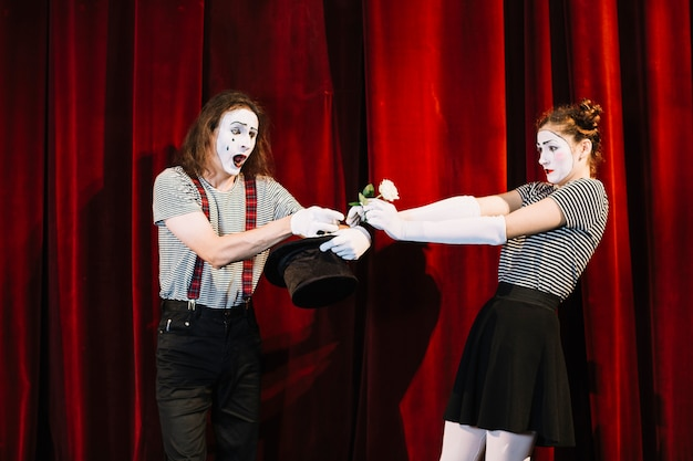 Two mime artist performing on stage in front of red curtain