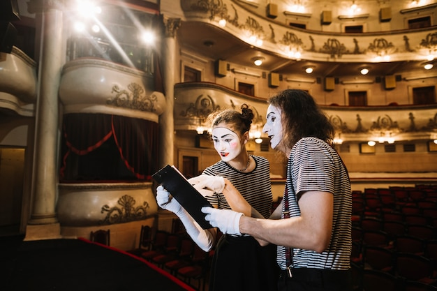 Two mime artist reading manuscript on stage