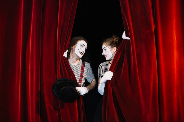 Two mime artist behind red curtain looking at each other