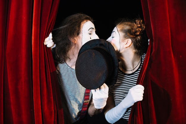 Two mime artist standing behind curtain kissing