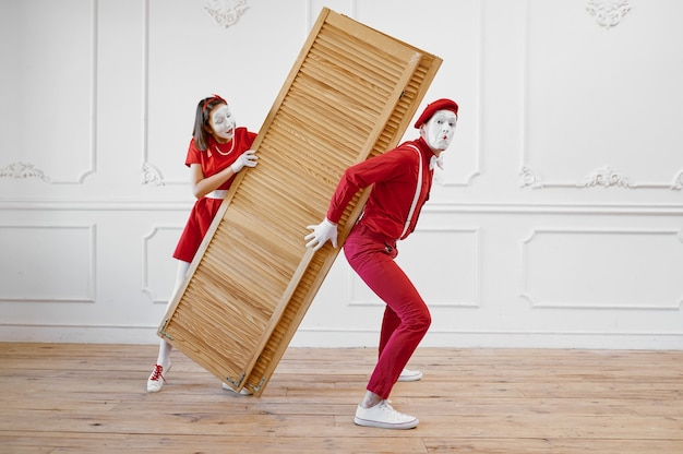 Two mime artists, clowns with wooden partition