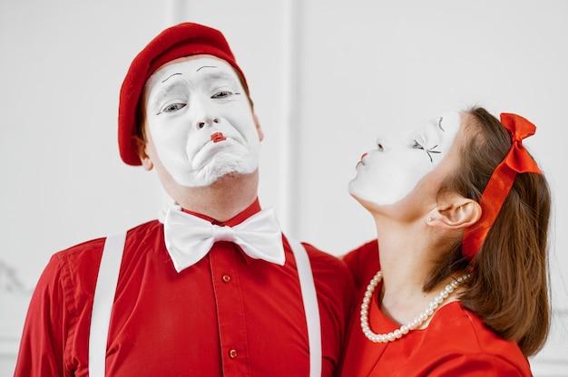Два артиста пантомимы в красных костюмах, сцена поцелуя
