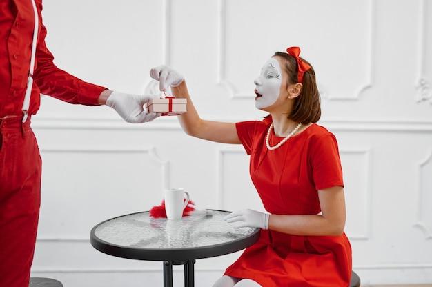 Два артиста пантомимы в красных костюмах, сцена с подарком