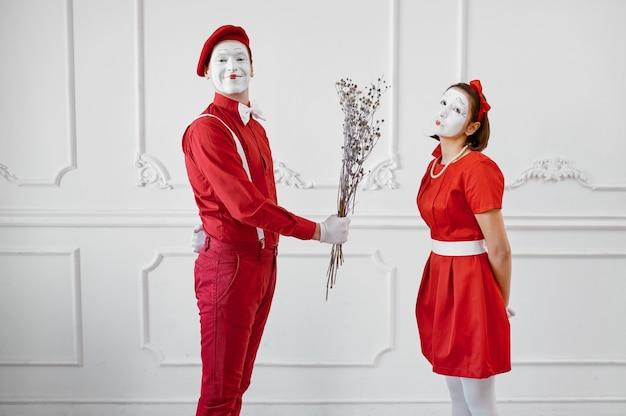 Два артиста пантомимы в красных костюмах, сцена с букетом