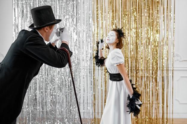 Два пантомима, дама позирует джентльмену с камерой