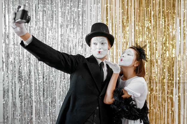 Two mime artists, lady poses at gentleman with camera