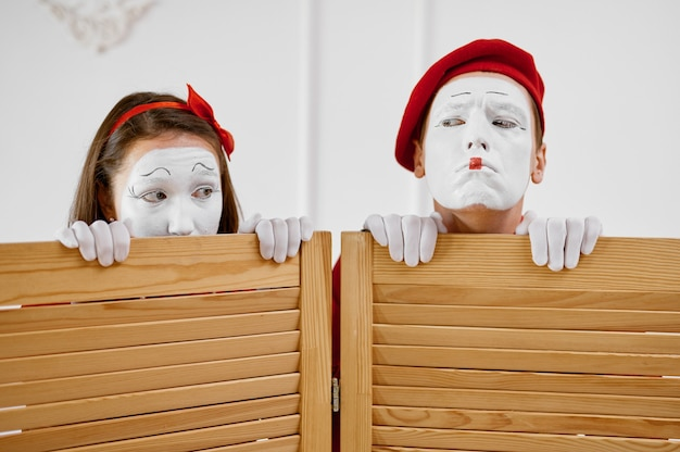 Two mime artists look out from partition