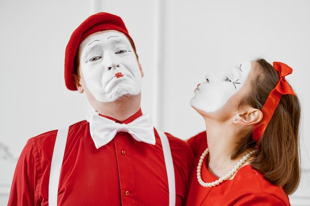 Two mime artists in red costumes, kissing scene