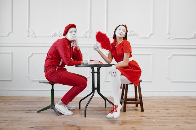 Two mime artists in red costumes, scene at the table