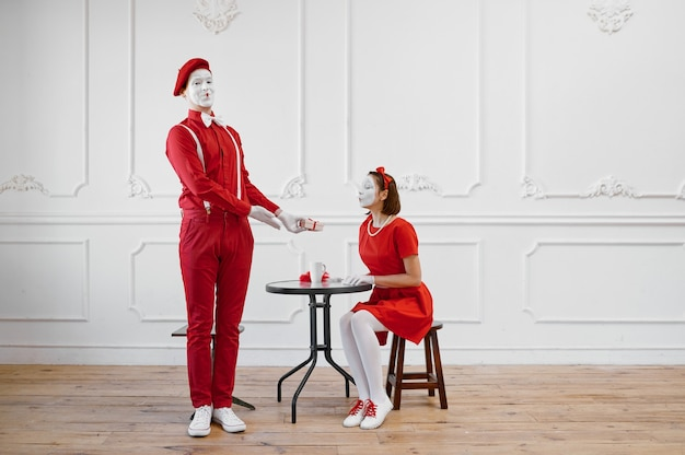 Two mime artists in red costumes, scene with gift
