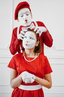 Two mime artists with face and hand makeup, red costumes