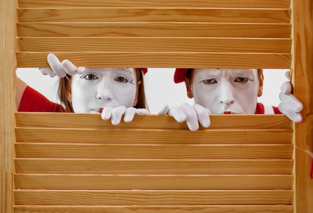 Two mime artists with makeup look through wooden partition