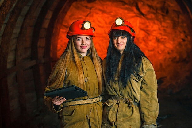 Two miners in the mine. girls in red helmets and lanterns in a coal mine.