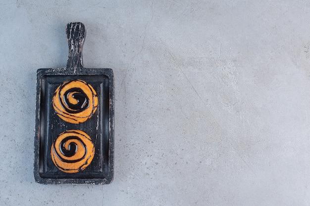 黒板にチョコレート釉薬で飾られた2つのミニケーキ。