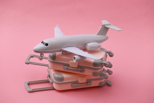 Two mini travel luggage suitcase and air plane on pink. travel still life, vacation or tourism concept.