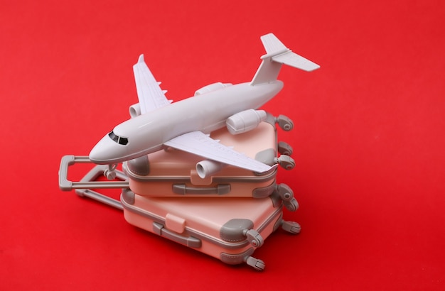 Two mini travel luggage suitcase and air plane on red. travel still life, vacation or tourism concept.