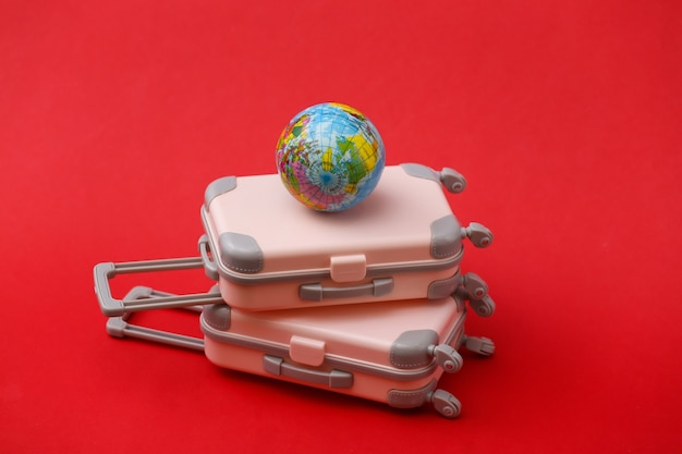 Two mini travel luggage suitcase and globe on red. travel still life, vacation or tourism concept.