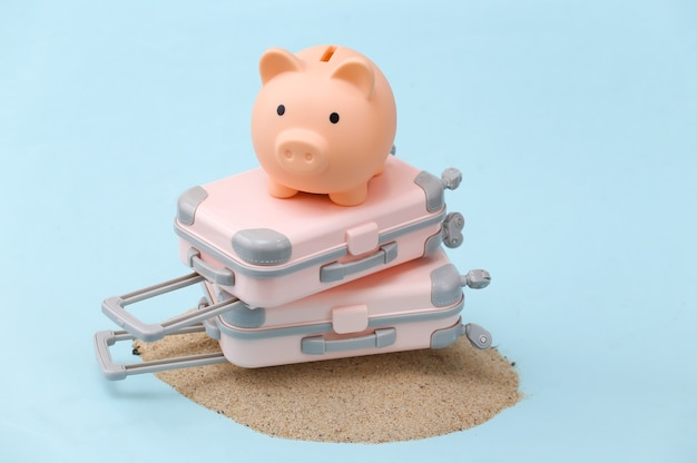 Two mini travel luggage suitcase and piggy bank on a sand island. travel, beach vacation concept